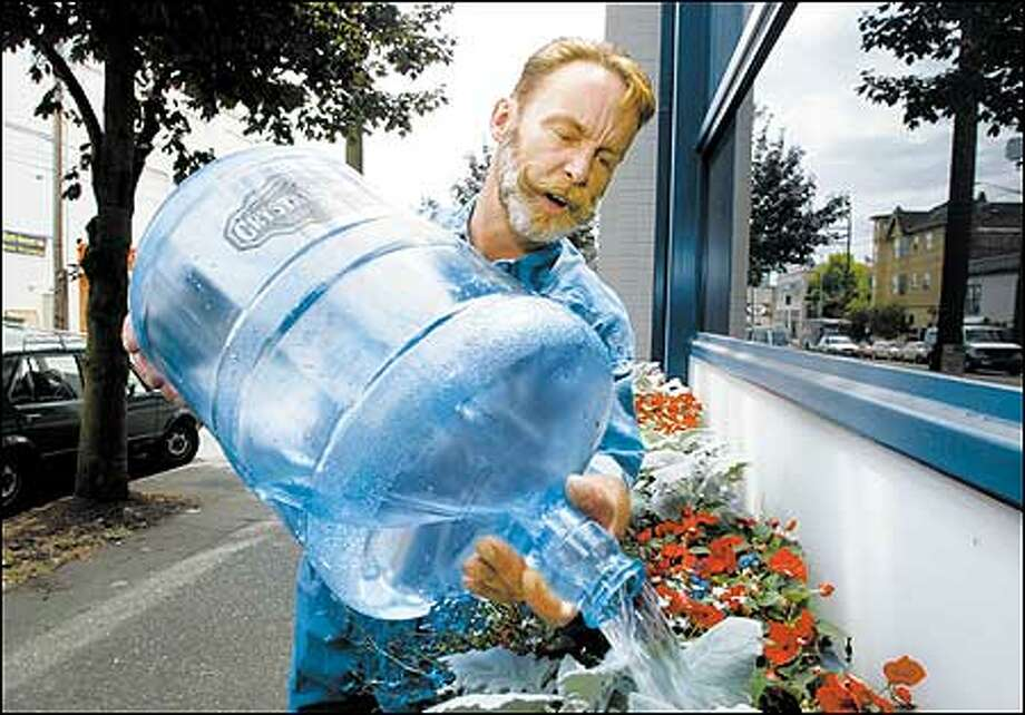 Maxcy Moon convinced Seattle Police and City Council members to let him plant flowers in front of the East Precinct police station. He transports tap water in these plastic containers. Photo: Gilbert W. Arias, Seattle Post-Intelligencer / Seattle Post-Intelligencer