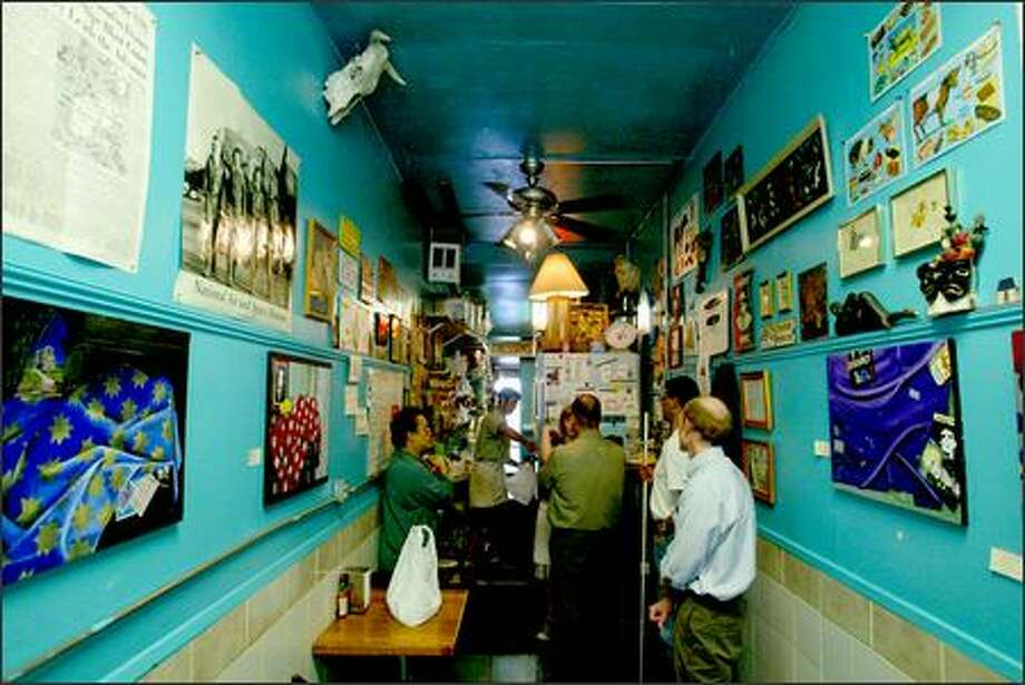 Customers can enjoy the funky artwork and curios that line the narrow walls at Roy's BBQ. Photo: Scott Eklund, Seattle Post-Intelligencer / Seattle Post-Intelligencer