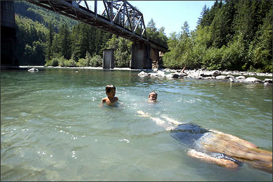 Jo Gerard from Sultan shows her son Jason Gerard, 5, how to swim like a shark in the Skykomish River. The Snohomish County Public Utility District has given up plans for a hydro project at Sunset Falls on the South Fork of the Skykomish River. Photo: Karen Ducey, Seattle Post-Intelligencer / Seattle Post-Intelligencer