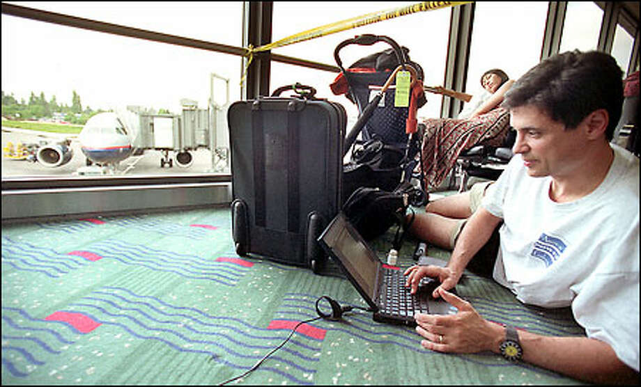 Russ Schifo works at his laptop at Sea-Tac Airport while waiting for a United Airlines flight home to Chicago. The flight was delayed because of thunderstorms in the Midwest. Photo: Paul Joseph Brown, Seattle Post-Intelligencer / Seattle Post-Intelligencer