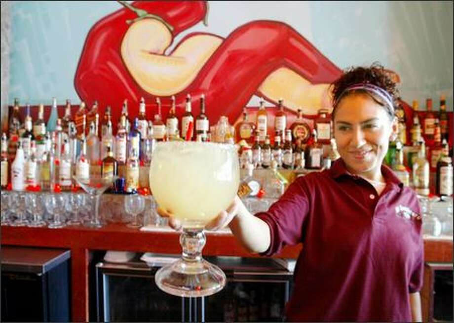 Maria Roman holds one of the huge house margaritas at El Sombrero Family Mexican restaurant in the Columbia City area. Be prepared to wait for seating in the popular eatery. Photo: Scott Eklund, Seattle Post-Intelligencer / Seattle Post-Intelligencer
