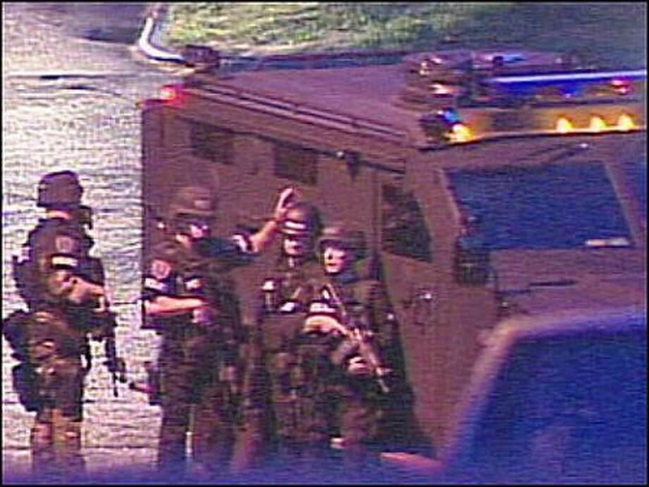Seattle police SWAT team members wait outside a Leschi residence late Wednesday night during negotiations with the suspected gunman in a fatal shooting. Photo: KOMO-TV/4 / KOMO-TV/4
