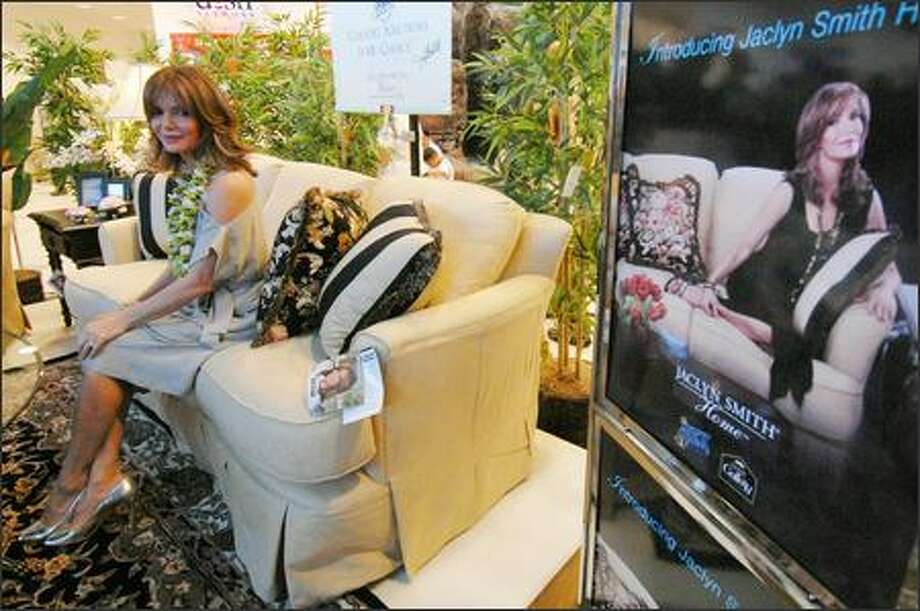 Actress Jaclyn Smith sits on one of her sofas at a store in Hawaii. Smith's furnishings line also includes wood furniture, bedding and fabric. Photo: Associated Press / Associated Press