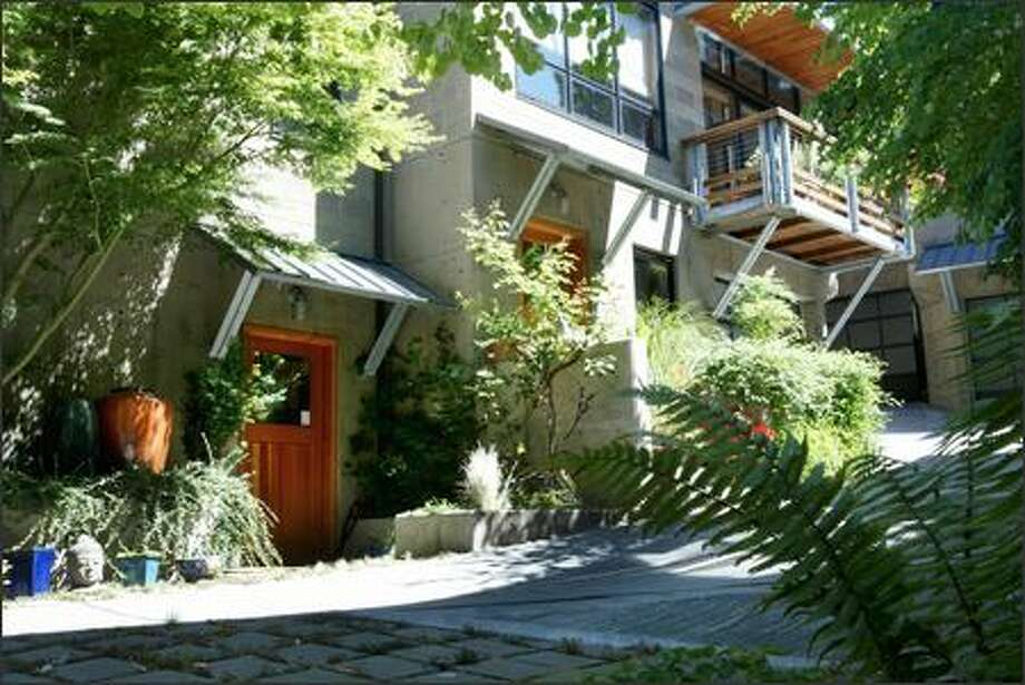 A winding driveway that serves as a pedestrian passage and a courtyard gives the Fremont Lofts townhomes the feel of a small European village. Mature landscaping adds to the serenity of the eight homes. Photo: Dan DeLong, Seattle Post-Intelligencer / Seattle Post-Intelligencer