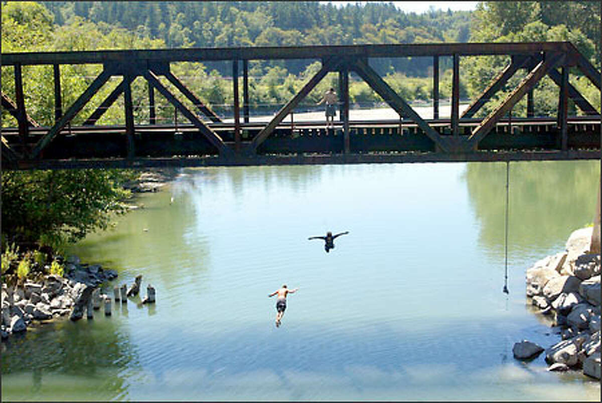 A group of friends enjoy the warm weather while jumping from a train bridge into the Stillaguamish River just off Pioneer Highway near Stanwood. Everyone knows the dangers. That's the edge.