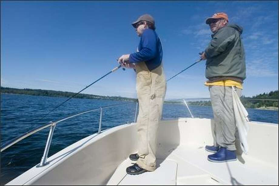 Puget Sound fishing guide Keith Robbins, right, works with Ken Willitts. Robbins emphasizes catch-and-release fishing. Photo: Jim Bryant, Seattle Post-Intelligencer / Seattle Post-Intelligencer