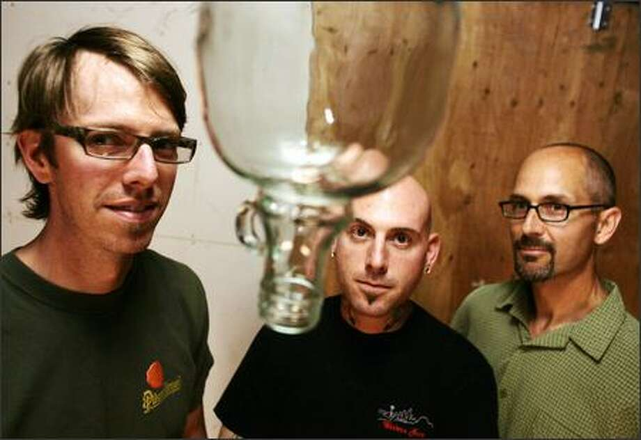 From left, Western Neon lead designer Marc Lawrence, lead fabricator Jaime Zaretsky and company president Jay Blazek uncorked their talents to create whimsical furniture out of empty wine jugs and glowing neon. Photo: Mike Kane, Seattle Post-Intelligencer / Seattle Post-Intelligencer