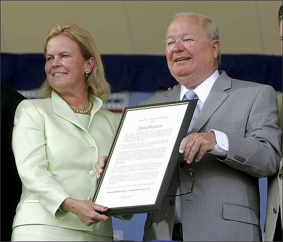 Mariners announcer Dave Niehaus holds the Ford C. Frick Award for baseball broadcasting, along with Jane Forbes Clark, chairman of the Baseball Hall of Fame, during Sunday's induction ceremony in Cooperstown, N.Y. Photo: Associated Press / Associated Press