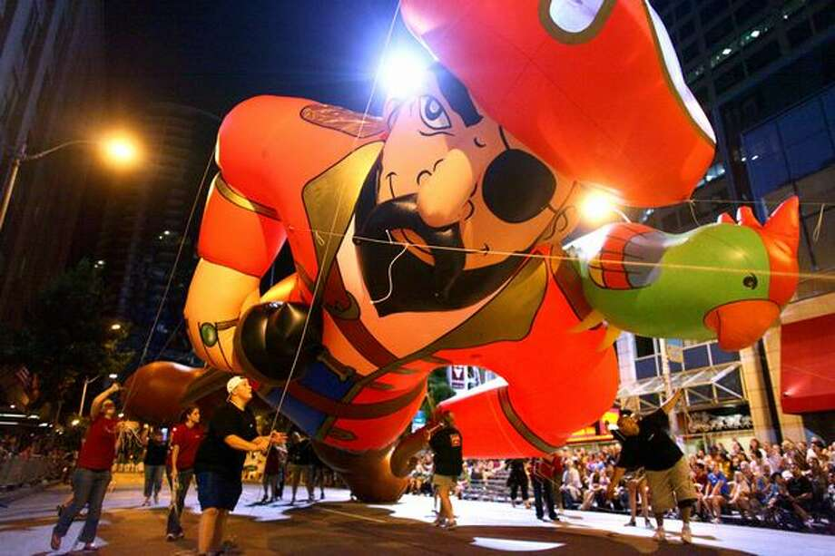 A towering inflatable pirate ducks under a cable along 4th Avenue during the Seafair Torchlight parade on Saturday. Photo: Joshua Trujillo, Seattlepi.com / seattlepi.com