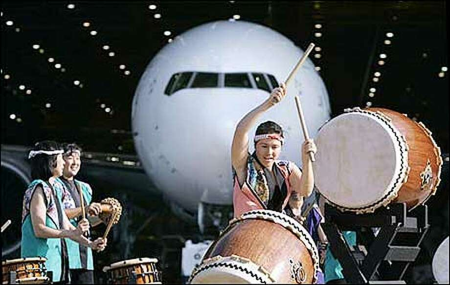 Taiko drummer Gretchen Ludwig performs with other members of Seattle Kokon Taiko as a new Boeing 777-300ER moves behind them in a ceremonial rollout Wednesday  in Everett. The plane was being delivered to Japan's  All Nippon Airways, the first 777-300ER the airline has purchased. Boeing  reported a better-than-expected $607 million profit for the second quarter and raised its earnings estimates for the rest of this year and next, buoyed in part by an improving outlook for the long-stagnant commercial airplane business. (AP Photo/Elaine Thompson) Photo: Associated Press / Associated Press