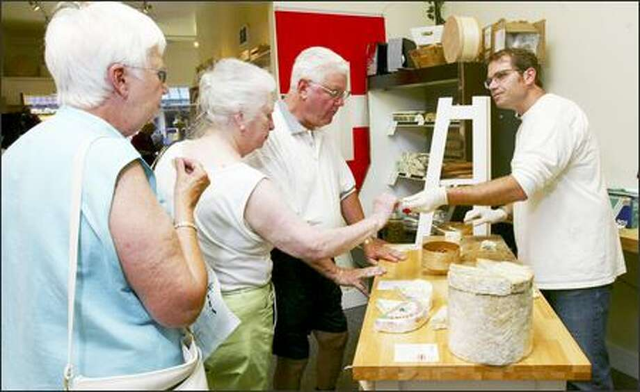 Resident Cheesemonger owner Strom Peterson, right, hands out a sample of Maytag Blue cheese to Birgit Lyshol, center, of Edmonds, with Verna and Bruce Amy of Woodway. Photo: Grant M. Haller, Seattle Post-Intelligencer / Seattle Post-Intelligencer