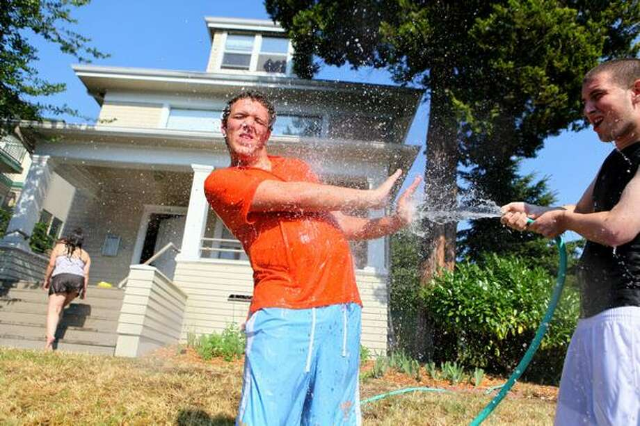 Tyler Peterson cools off his roomate Billy Bones, left, outside of the sweltering home they share on 15th Avenue Northeast in Seattle on Tuesday. Photo: Joshua Trujillo, Seattlepi.com / seattlepi.com