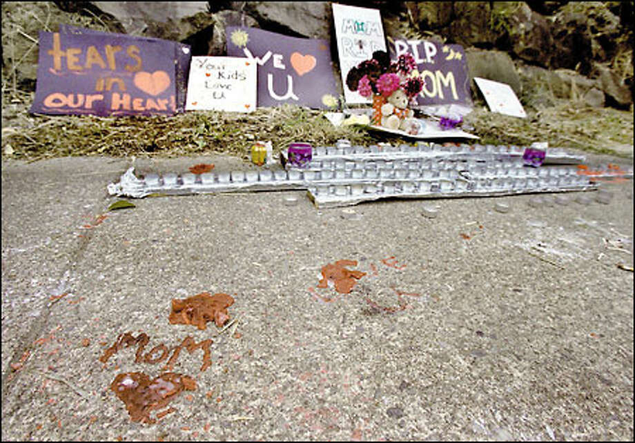 The slain woman's family created a memorial of candles and messages at the rockery where her body was found. Photo: Renee C. Byer, Seattle Post-Intelligencer / Seattle Post-Intelligencer