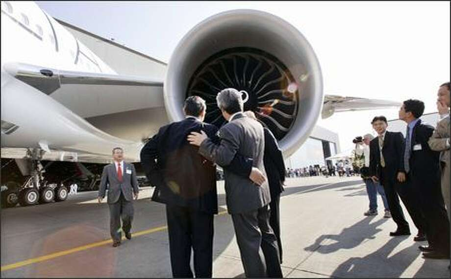 Officials of All Nippon Airways look into an engine of their new Boeing 777-300ER following a ceremonial rollout in Everett. The plane was being delivered to the Japanese airline, the first 777-300ER that it has bought. The Boeing Co. reported a better-than-expected $607 million profit for the second quarter and raised its earnings estimates for the rest of this year and next, buoyed in part by an improving outlook for the long-stagnant commercial airplane business. Photo: Associated Press / Associated Press