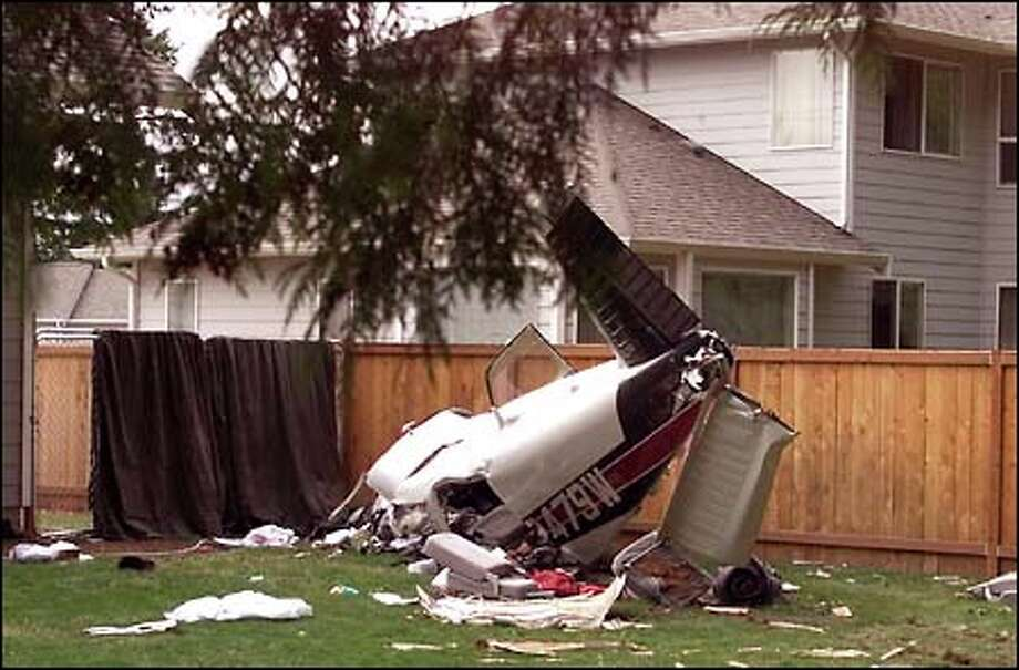 The wreckage of a small plane lies in the back yard of a home in Puyallup, a little more than a mile from the end of the runway at Pierce County Airport. Photo: Gilbert W. Arias, Seattle Post-Intelligencer / Seattle Post-Intelligencer