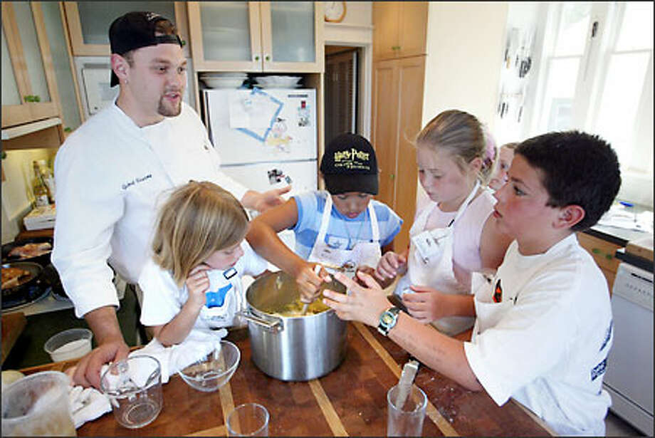 Gabriel Claycamp watches as some of his students -- Alexis Allen, 9, Zoe Brown, 9, Alexis Allen, 9, Clair Miller, 10, and Josh Kantor, 10 -- sample the polenta during their cooking class Photo: Scott Eklund, Seattle Post-Intelligencer / Seattle Post-Intelligencer