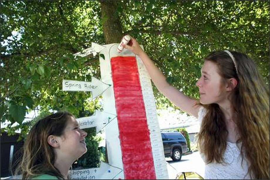 Laura D'Asaro of Seattle marks off yet another attained goal as she and Haley Lowe sell cookies and lemonade from a stand on the Burke-Gilman Trail to raise money for playground equipment. Photo: Karen Ducey, Seattle Post-Intelligencer / Seattle Post-Intelligencer