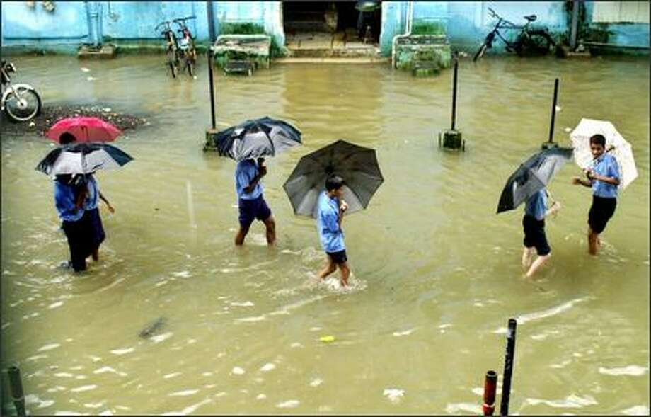 School children walk through floodwaters in Bombay, India. The death toll from monsoon flooding in India crossed 1,000 Wednesday with reports of almost 150 people killed in the country's west and north, as rains destroyed crops, flooded highways and halted trains in South Asia. (AP Photo/Rajesh Nirgude) Photo: Associated Press / Associated Press