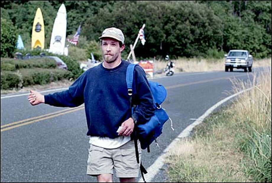 Orcas Island resident Paul Carroll hitchhikes home from work outside the village of Eastsound. He said someone usually picks him up within five or 10 minutes. Photo: Dan DeLong, Seattle Post-Intelligencer / Seattle Post-Intelligencer