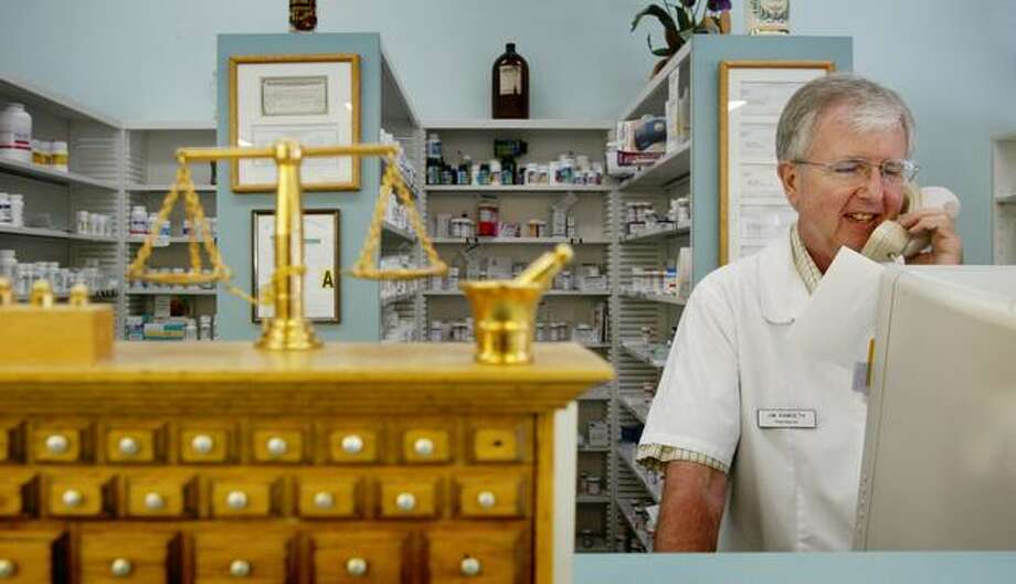 Pharmacist Jim Ramseth, then-owner of the Covington Pharmacy, answers a customer's question regarding a prescription in this August 2006 file photo. Ramseth was among those who felt they should not be forced to dispense the emergency contraception pill Plan B before he retired in November 2009. Photo: P-I File / P-I File