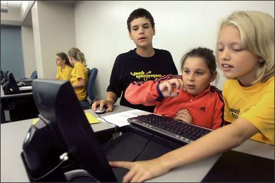 John Deangelis, left, 15, helps Emily Sauser and Caitlin Novak, both 11, with a business plan presentation at an entrepreneurs summer camp. Photo: New York Times / New York Times
