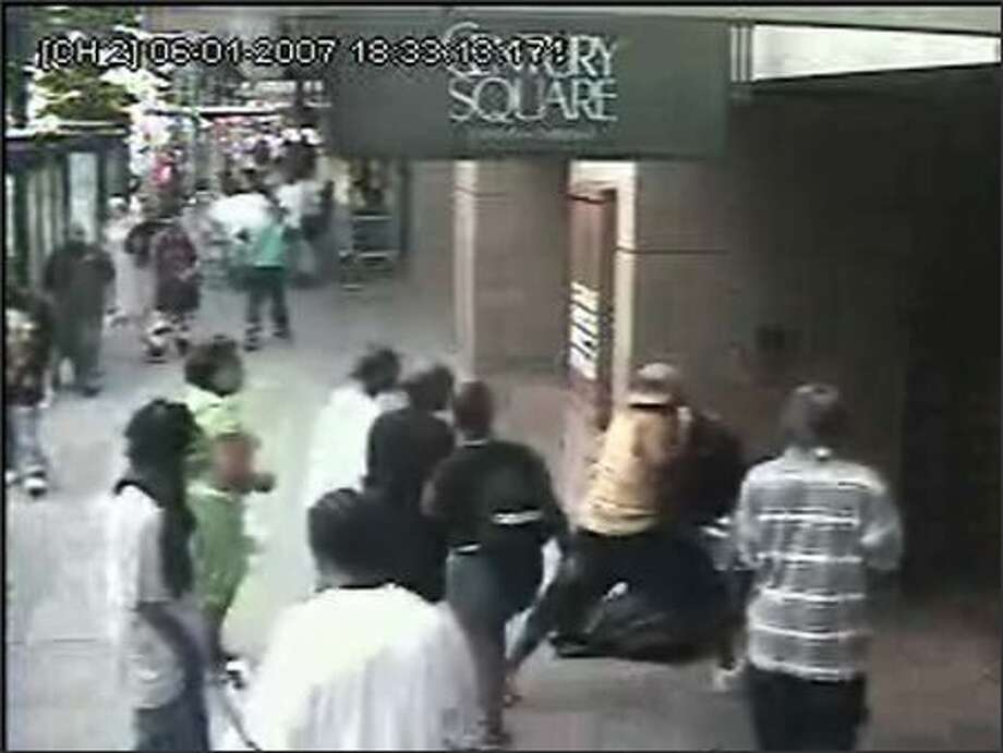 A security camera captures the June 1 beating of a man outside the Century Square building near Third Avenue and Pine Street by a group of youths. The man was hospitalized, then released. (SEATTLE POLICE DEPARTMENT)