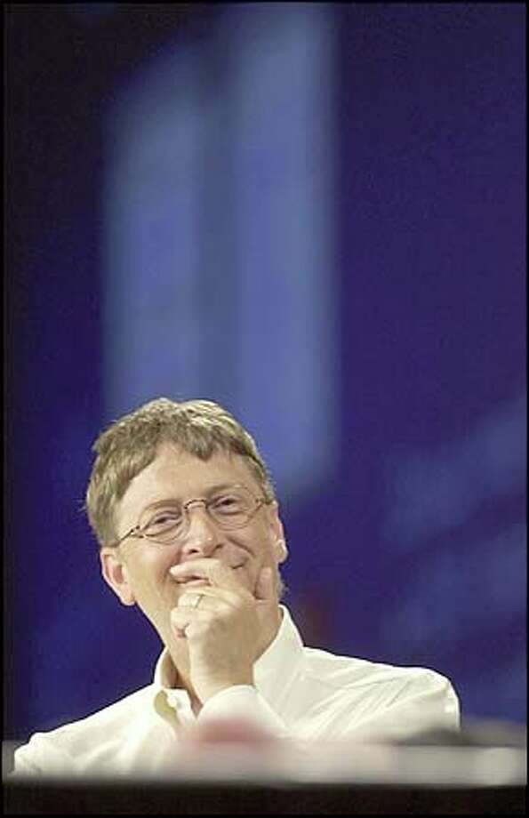 A bemused Microsoft Chairman Bill Gates watches a demonstration during his address at the AI session Tuesday. Photo: Associated Press / Associated Press