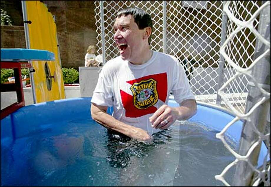 Seattle police Chief Gil Kerlikowske emerges from the dunk tank yesterday at the Public Safety Building's Memorial Plaza. The chief was helping raise money for Special Olympics during the noon hour. Photo: Meryl Schenker, Seattle Post-Intelligencer / Seattle Post-Intelligencer