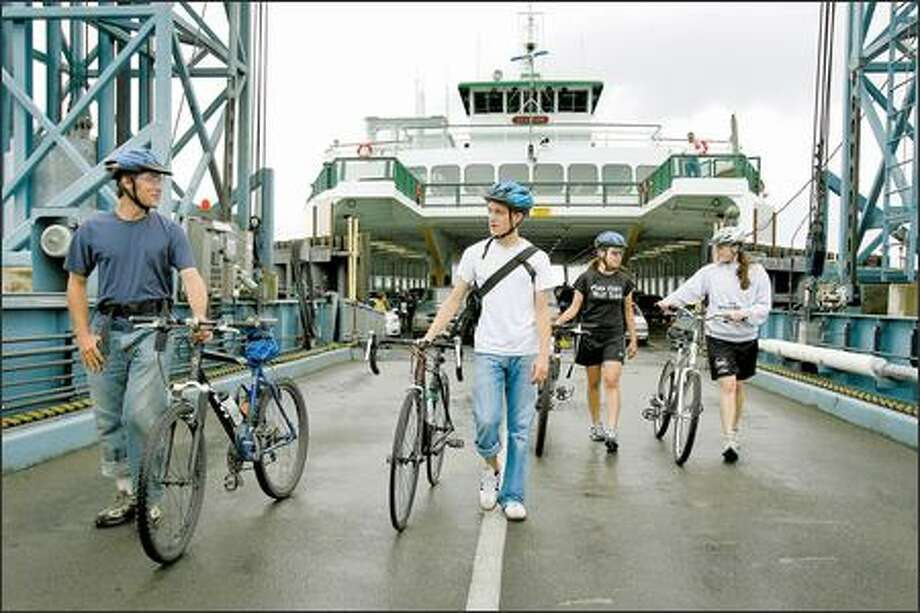 Ready to roll: Ethan Welty, left, Brandt Scanlan, Adrienne Oda and Meghan Peters offload the ferry Tillicum on Vashon Island. Photo: Mike Urban, Seattle Post-Intelligencer / Seattle Post-Intelligencer