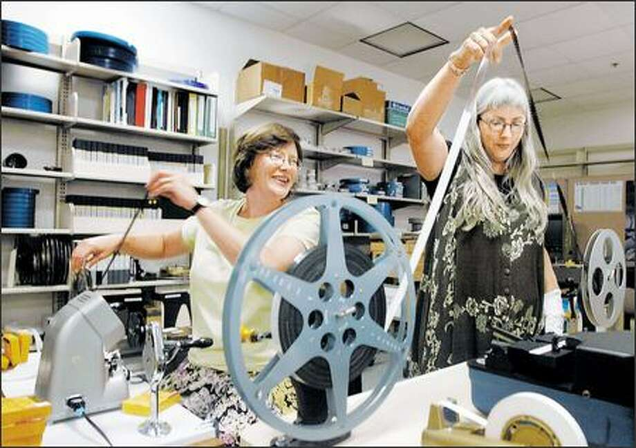 Hannah Palin, left, and Libby Burke keep the tape rolling for the University of Washington's Film Preservation Project. Photo: Meryl Schenker, Seattle Post-Intelligencer / Seattle Post-Intelligencer