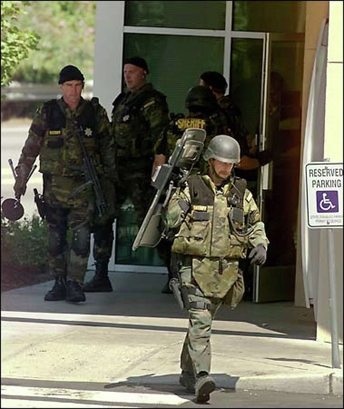SWAT team members leave the Bank of America branch across from Sea-Tac Airport after determining a suspected robber was no longer inside.