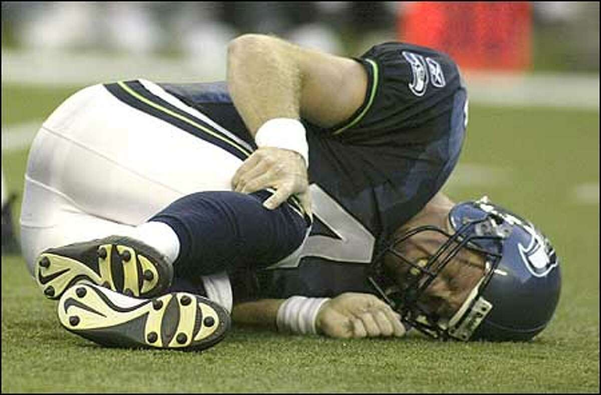 Seahawks quarterback Trent Dilfer lies on the field and grabs his right knee after being hit by Indianapolis Colts defenders early in the second quarter. Dilfer, who sprained his knee, was helped off the field by team trainers and replaced by Matt Hasselbeck.
