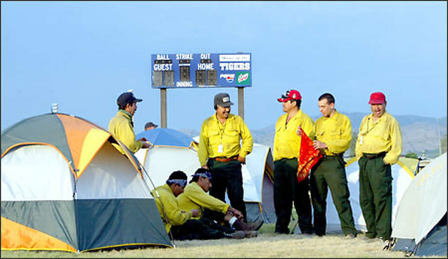 Wildfire crews may be bunked at Tonasket High School's baseball field, but they make their way into town, contributing to a boom that will live as long as the fire does. Photo: Karen Ducey, Seattle Post-Intelligencer / Seattle Post-Intelligencer