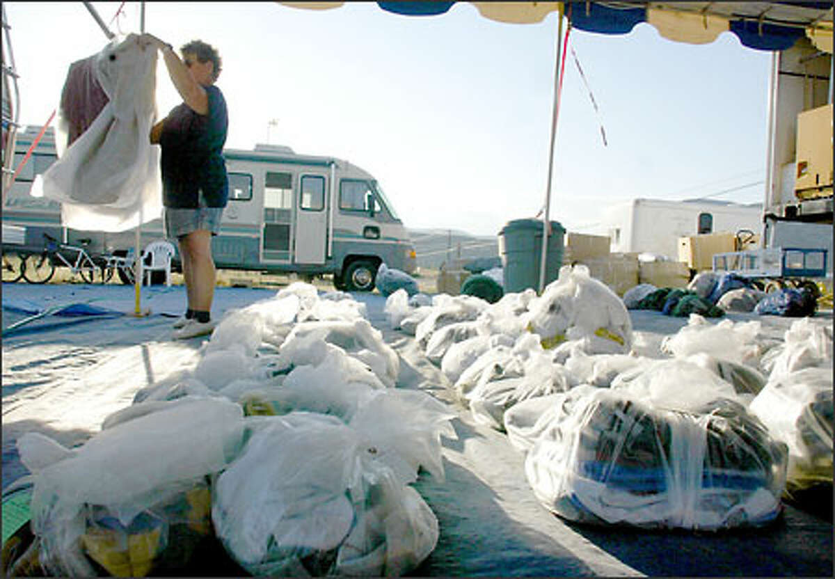 Patt Nottier of All States Fire Support, a mobile laundry service, sorts through laundry at the fire camp in Tonasket. The crew she works with can clean up 200 pounds of dirty clothes an hour.