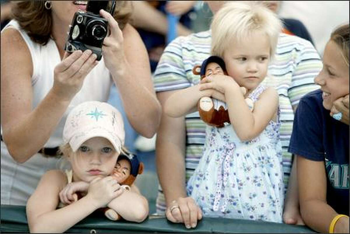 Courtney Dietrich, 6, of Aberdeen, left, and Melanie Love, 2, of Seattle, hang onto their Edgar Martinez dolls at last night's M's-Twins game at Safeco Field. Martinez, who announced his retirement Monday, provided another memory for his fans by hitting a homer in a 4-3 M's win.
