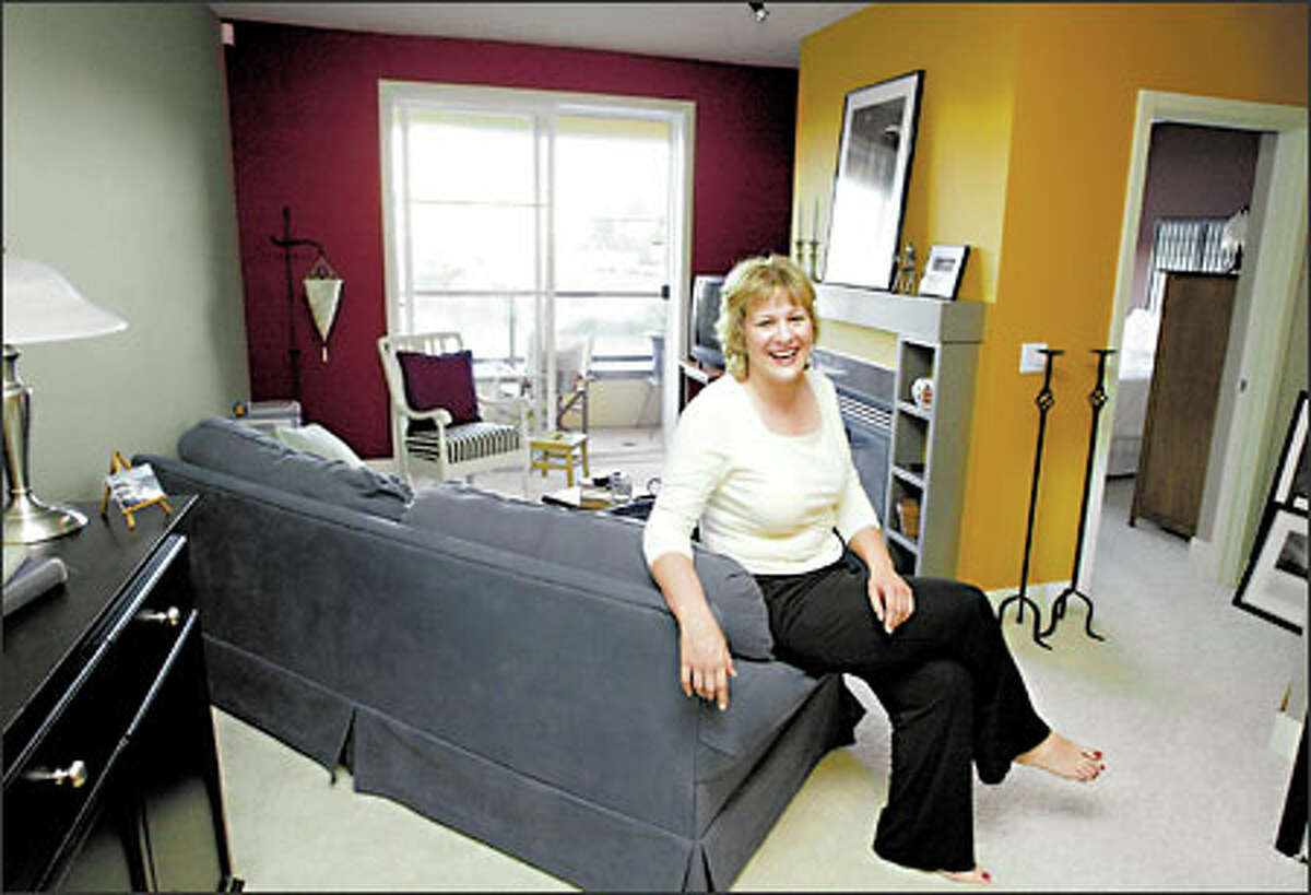 AFTER: Jane Turlo revels in her colorful condo done in, from left, Waynesboro Taupe, Arroyo Red and Gold Mine. Next up is a furnishings makeover, starting with a new couch.