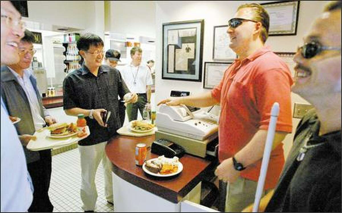Robert Ott, in red shirt, has operated the Modern Day Cafe at the Seattle campus of the National Oceanic and Atmospheric Administration since 1995. Ott, who's been blind since 1990, is leaving to run a cafeteria at Fort Lewis. Chad Morey, at right, who is also blind, will take over.