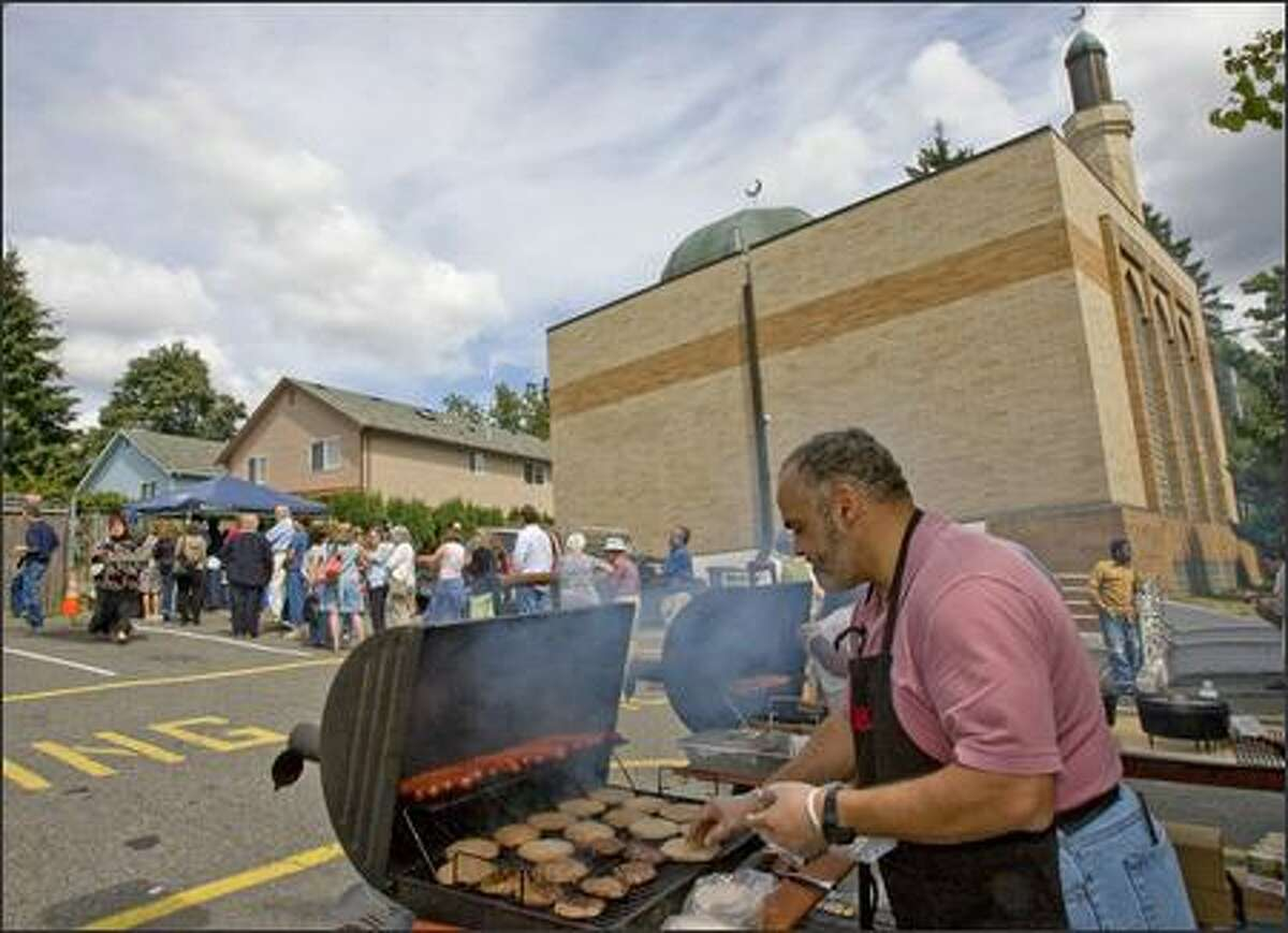Ashraf Abdel-Rassoul turns out hot dogs and hamburgers Sunday at Idriss Mosque's annual Northgate barbecue, which started as a post-9/11 thank you to neighbors and is now a multifaith event.