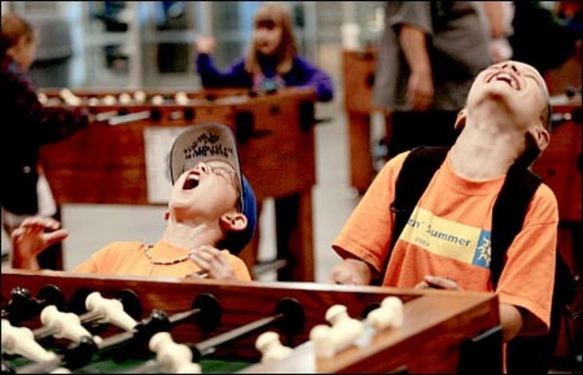 Joshua Host, 8, left, of Redmond and Andrew Soshea, 7, of Woodinville get a charge out of playing foosball yesterday at the first-ever GameFest for members of the Boys & Girls Clubs of King County in the Stadium Exhibition Center. The games continue today in the center and at Seahawks Stadium.