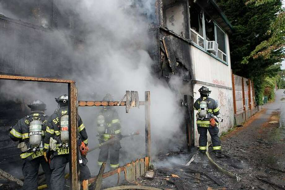 Firefighters douse the smoldering remains of a Greenwood house after putting out a fire Thursday. Photo: Clifford DesPeaux, Special To The Seattle Post-Intelligencer / Special to the Seattle Post-Intelligencer