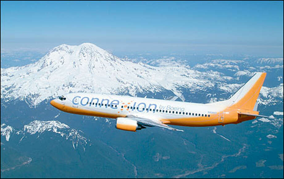 The Boeing Co. will use its familiar orange tester plane -- here flying by Mount Rainier -- to demonstrate its broadband communications service. Photo: The Boeing Company / The Boeing Company