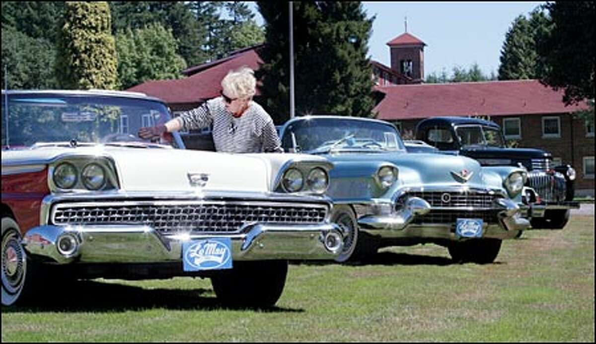 Volunteer Gayle Harris of Puyallup dusts off a 1959 Ford Galaxie with a retractable hardtop. Also pictured are a 1955 Cadillac Eldorado and a 1946 Chevrolet 1-ton farm truck.