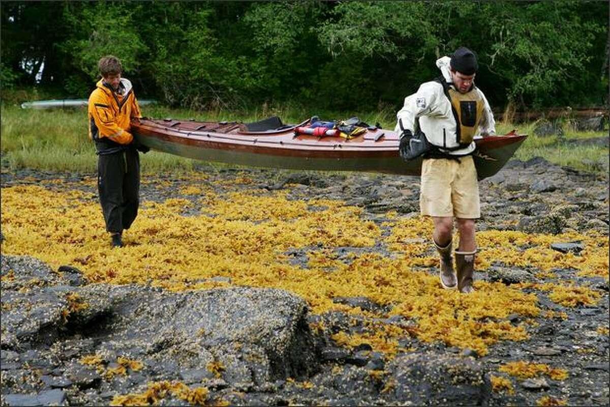 Jonathan Hayes, left and Colin McDonald, right, carrying Hayes' kayak to the water. Michael Naiman