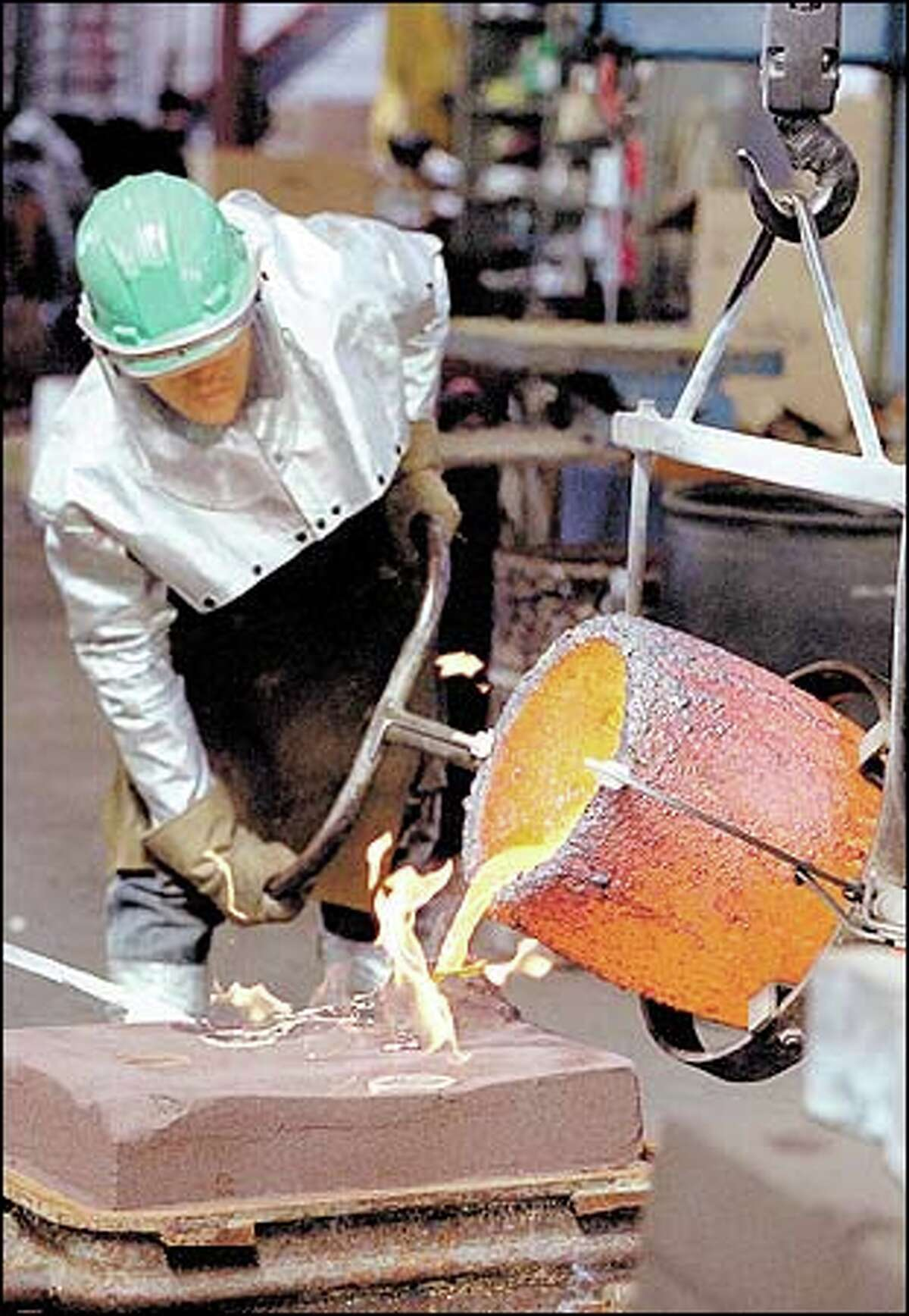 Aaron Combs, a melter/molder for Irish Foundry under the West Seattle viaduct, pours bronze into a mold.