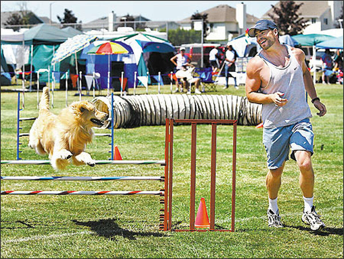 Dan Butcher of Portland smiles at Tommy, his golden retriever, as they finish the agility course during an Enumclaw competition. Tommy looks happy too.
