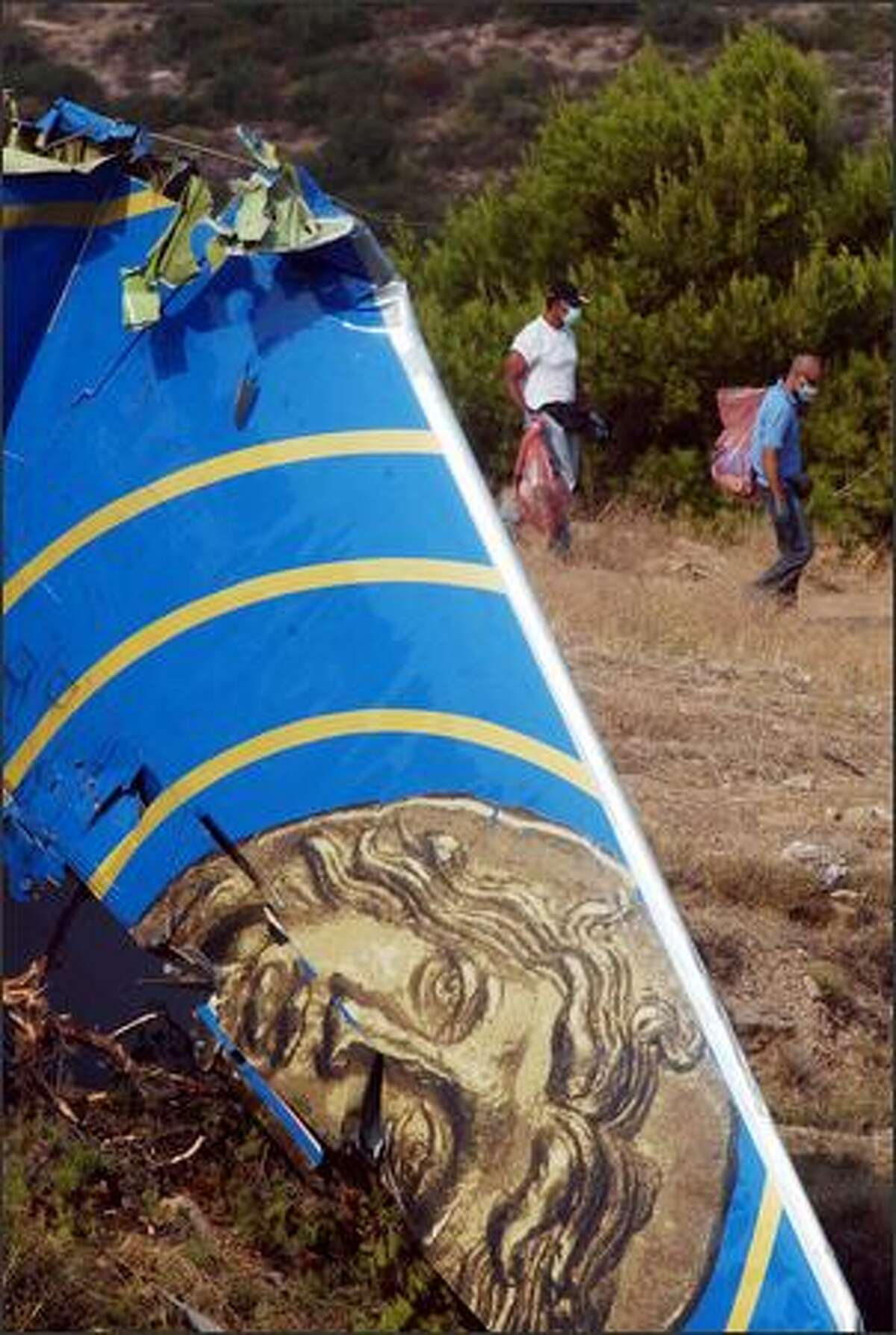The tail of a Cypriot airliner is seen as investigators carry plastic bags at the crash site where the aircraft slammed into a hill, in the coastal town of Grammatiko, Greece on Monday, Aug. 15, 2005. The Helios Airways Boeing 737 crashed 40 kilometers (25 miles) north of Athens after an apaparent loss of cabin pressure, all 121 people on board were killed . (AP Photo/Thanassis Stavrakis)