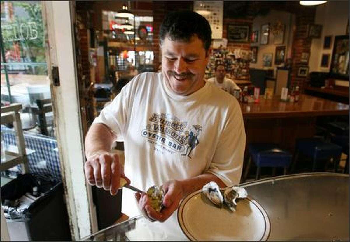 Owner Thurman Bryant shucks an oyster at Emmett Watson's Oyster Bar.