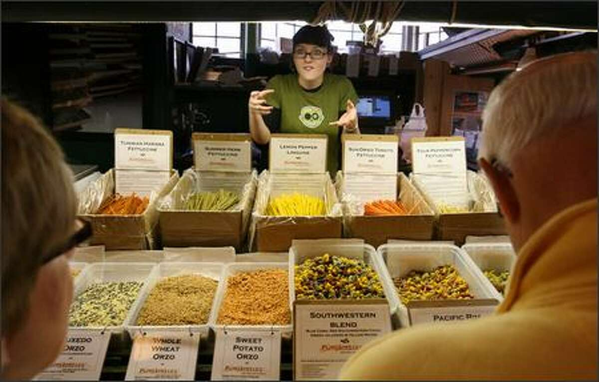 Ruth Conley of Pappardelle's Pasta talks enthusiastically to passing shoppers about the unusual variety of pastas they offer.