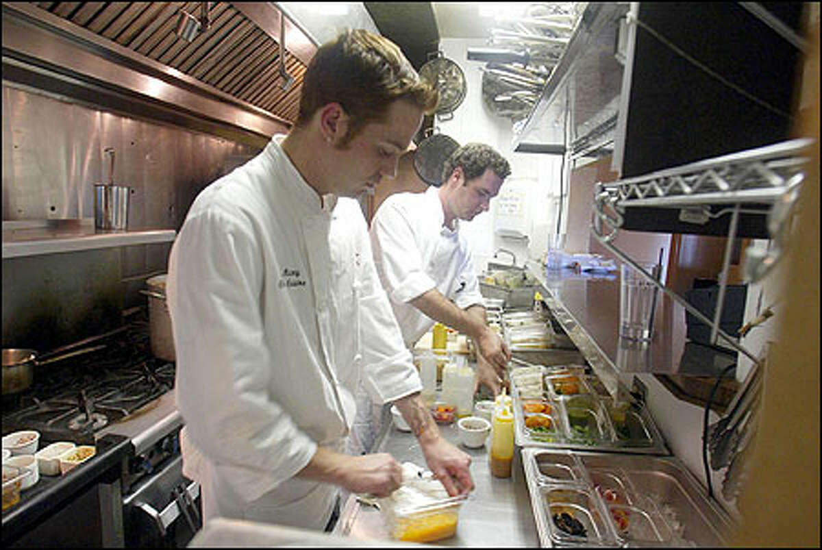 Sean Maxey, chef de cuisine, left, and Patrick Sullivan, line cook, prepare their mis en place (the ingredients needed to prepare menu items) in the kitchen at Fira on Queen Anne.