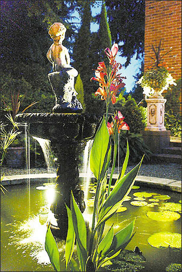 It's not just for security anymore: Outdoor lighting also is seen as an art form that creates a mood by highlighting architectural and garden features. The lighting scheme for this fountain and pool was designed by Seattle landscape architect Brooks Kolb. Photo: Mike Urban, Seattle Post-Intelligencer / Seattle Post-Intelligencer